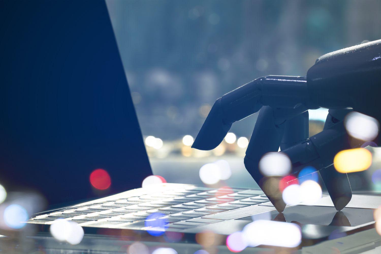 Roboter-Hand bedient Tastatur eines Laptops; Thema: KI in der Produktion