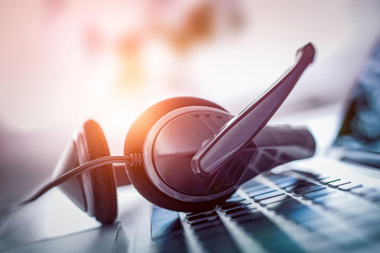 Headset liegt unbenutzt auf Computertastatur; Thema: Chatbots