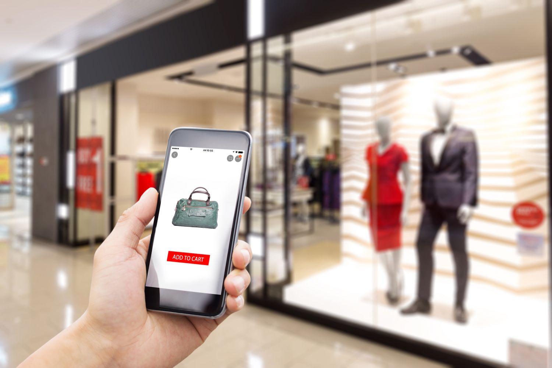 Smartphone mit Online Shop vor einem Ladengeschäft. Thema: Einzel- vs Onlinehändler