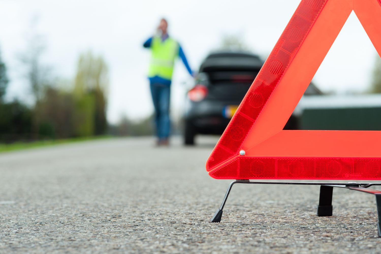 Mann telefoniert nach Autopanne; Warndreieck im Vordergrund