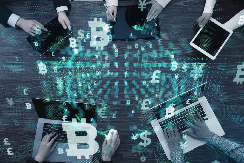 5 Personen sitzen mit Laptops und Tablets in der Hand an einem Tisch; Thema: Kryptogeld