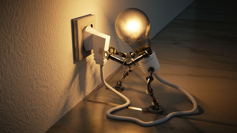 Ein Männchen mit Glühbirnenkopf steckt einen Stecker in eine Steckdose. Thema: Künstliche Intelligenz bei digitalen Business Cases
